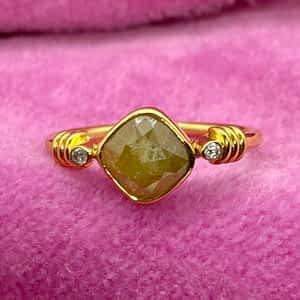 Guldring med stor grøn diamant og små hvide diamanter